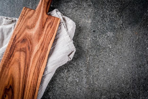 Kochen, altes hölzernes schneidebrett mit geschirrtuch auf schwarzer steintabelle. draufsicht, exemplar Premium Fotos