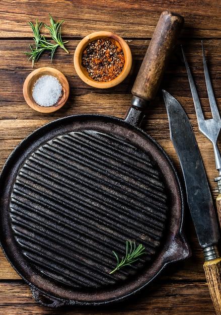 Kochen des hintergrundkonzeptes. vintagr eisen grillpfanne und besteck. ansicht von oben Premium Fotos