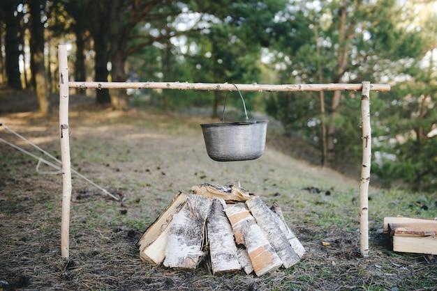Kochen unter feldbedingungen, kochtopf am lagerfeuer beim picknick. gefiltertes bild: kreuzverarbeiteter vintage-effekt. Premium Fotos