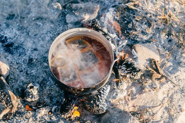 Kochendes wasser mit teepackungen im metalltopf im freien Premium Fotos
