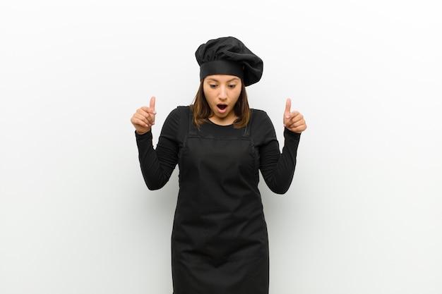 Kochfrau, die sich schockiert, mit offenem mund und erstaunt fühlt, ungläubig und überrascht gegen weiß schaut und nach unten zeigt Premium Fotos