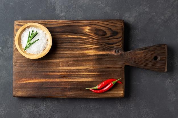 Kochkonzept. weinleseschneidebrett mit salz und rotem pfeffer auf dunklem steinhintergrund. Premium Fotos