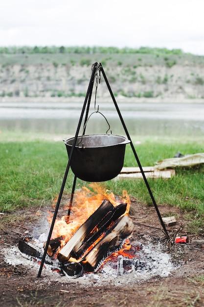 Kochtopf, der über brennendem brennholz hängt Kostenlose Fotos