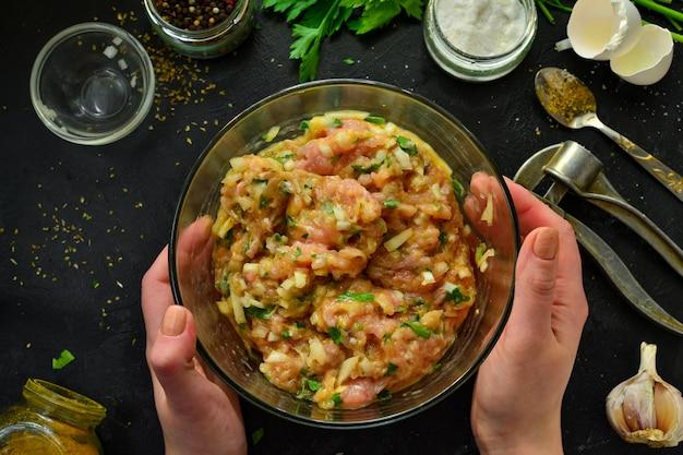 Kochvorgang. hackfleisch und zutaten, salz, pfeffer, gewürze, zwiebeln, eier, petersilie, mischen sie die zutaten mit einem löffel. eine frau bereitet hackfleisch für fleischbällchen vor. draufsicht. Premium Fotos