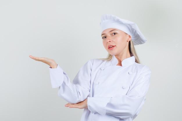 Köchin, die etwas in weißer uniform begrüßt oder zeigt und fröhlich aussieht Kostenlose Fotos