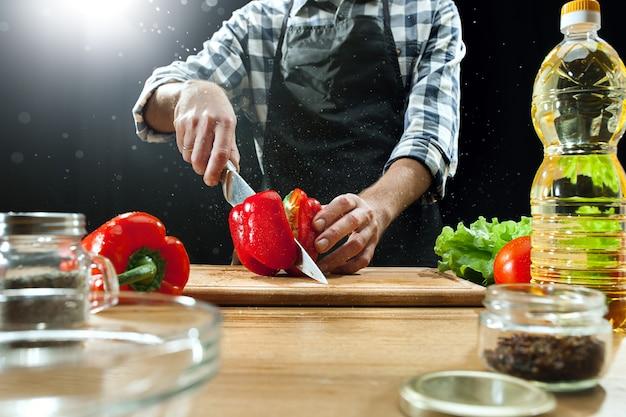Köchin, die frisches gemüse schneidet Kostenlose Fotos