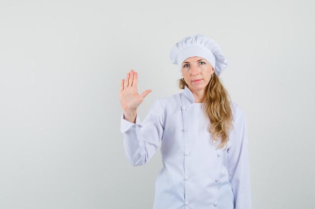 Köchin winkt hand, um sich in weißer uniform zu verabschieden und ruhig auszusehen Kostenlose Fotos
