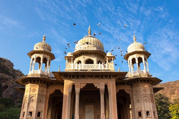 Königliche gaitore tumbas in jaipur indien mit dem vogel, der vorbei in blauen himmel fliegt. Premium Fotos