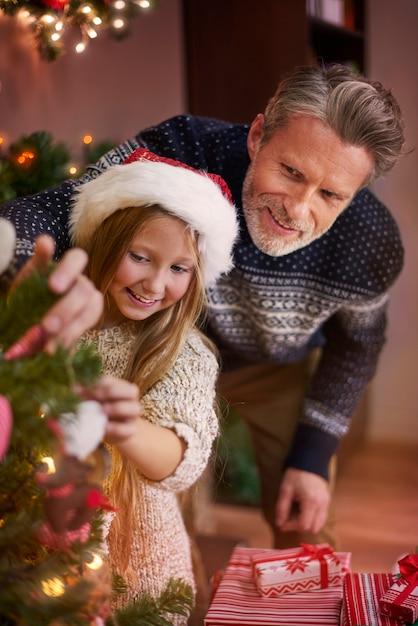 Können sie mir beim dekorieren des weihnachtsbaums helfen? Kostenlose Fotos