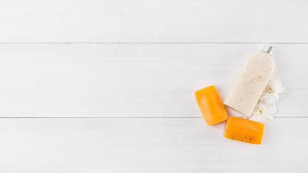 Körperpeeling-flasche; kräuterseife und weiße blume auf hölzernem plankenhintergrund Kostenlose Fotos
