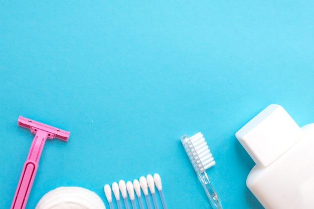 Körperpflegeprodukte. weiße flasche, rasiermesser, ohrstifte, wattepads, zahnbürste auf blauem ba Premium Fotos