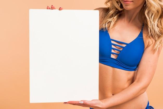 Körperteil der dünnen frau im blauen bikini mit leerem brett Kostenlose Fotos