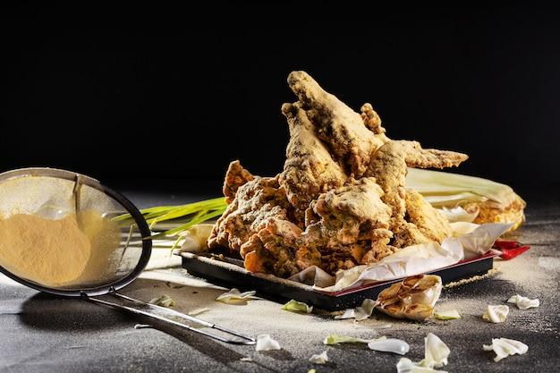 Köstlich gekochte und gewürzte hühnerflügel mit knoblauch auf dem tisch unter dem licht Kostenlose Fotos