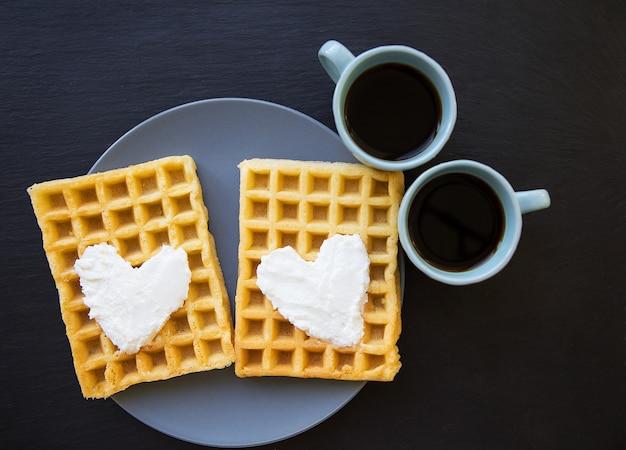 Köstliche belgische waffeln mit sahne auf einem schwarzen hintergrund und zwei tasse kaffees. Premium Fotos