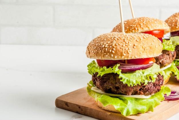 Köstliche frische geschmackvolle burger des ungesunden lebensmittels des schnellimbisses mit frischgemüse und käse des rindfleisch-koteletts auf weißem hintergrund Premium Fotos
