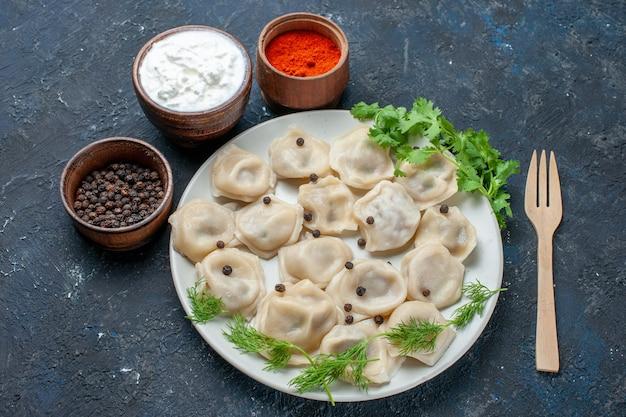 Köstliche gebackene knödel in teller zusammen mit joghurt und gemüse auf dunkelgrauem schreibtisch, abendessen fleisch kalorien mahlzeit essen Kostenlose Fotos