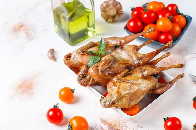 Köstliche gebratene wachtel mit kräutern und kirschtomaten. Kostenlose Fotos