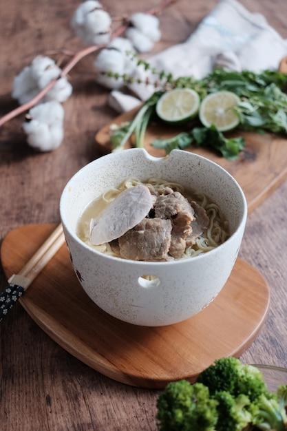 Köstliche geschmackvolle gelbe nudeln mit fleischbällchen auf der schüssel mit essstäbchen Premium Fotos