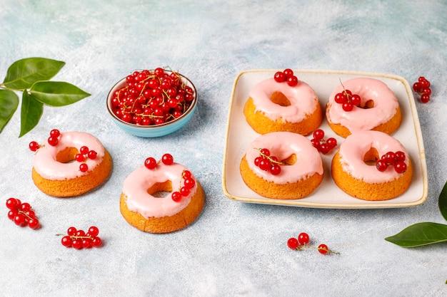 Köstliche hausgemachte glasur donuts mit roten johannisbeeren. Kostenlose Fotos