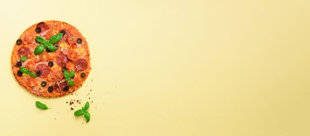 Köstliche italienische pizza, basilikumblätter, salz, pfeffer auf gelb Premium Fotos