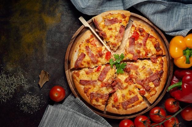 Köstliche italienische pizza schnitt schinken, speck und käse mit lebensmittelinhaltsstoffen auf alter küche Premium Fotos