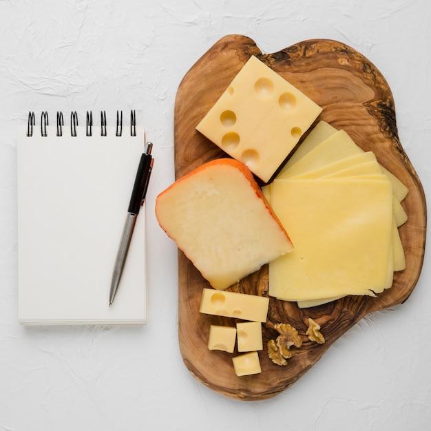 Köstliche käseservierplatte und leere gewundene molkerei mit stift gegen einfachen hintergrund Kostenlose Fotos