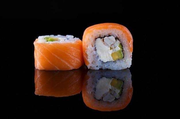 Köstliche kalifornien-sushirolle auf einem schwarzen hintergrund mit reflexion Premium Fotos