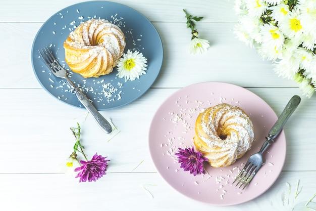 Köstliche kuchen mit kokosnusschips auf rosa und grauer platte auf weißer tabelle Premium Fotos
