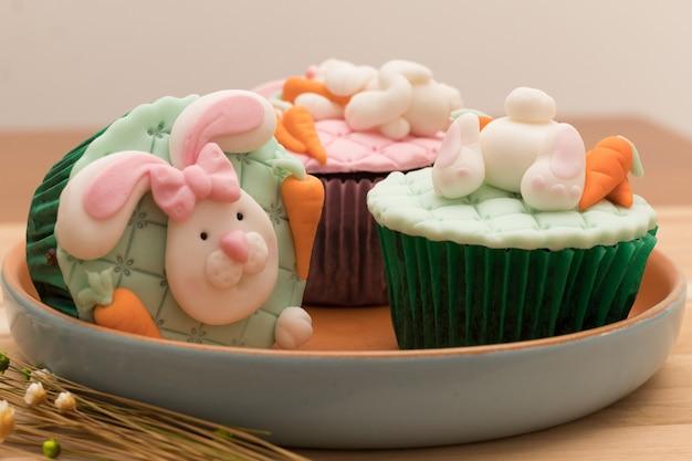 Köstliche ostern-kleine kuchen auf rustikaler platte und hölzernem hintergrund Premium Fotos