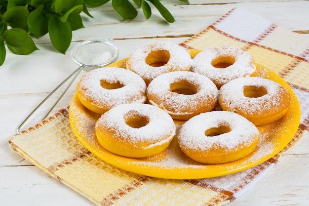 Köstliche schaumgummiringe auf gelber platte Premium Fotos