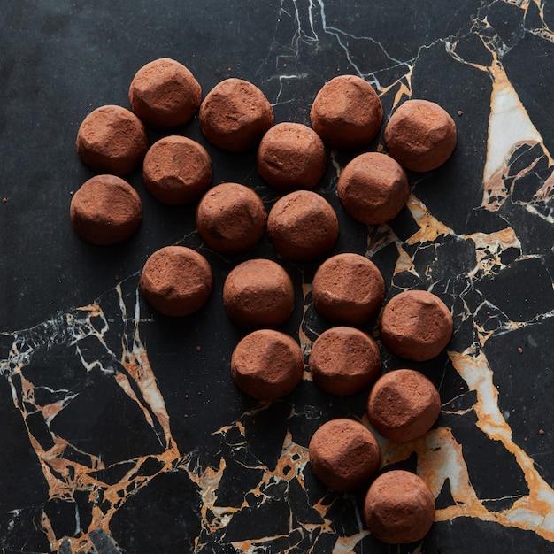Köstliche schokoladentrüffel auf dunkler marmoroberfläche Premium Fotos