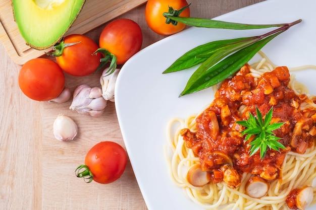 Köstliche spaghettis dienten in einer weißen platte auf hölzerner tabelle Premium Fotos