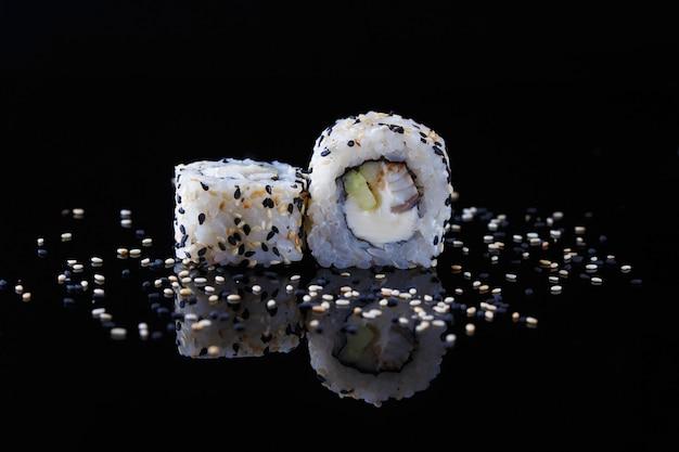 Köstliche sushirolle mit fischen und indischem sesam auf einem schwarzen hintergrund mit reflexion menü und restaurant Premium Fotos