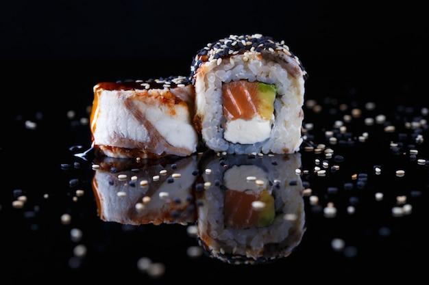 Köstliche sushirolle mit fischen und indischem sesam wässerte mit sojasoße auf einem schwarzen hintergrund mit reflexion Premium Fotos