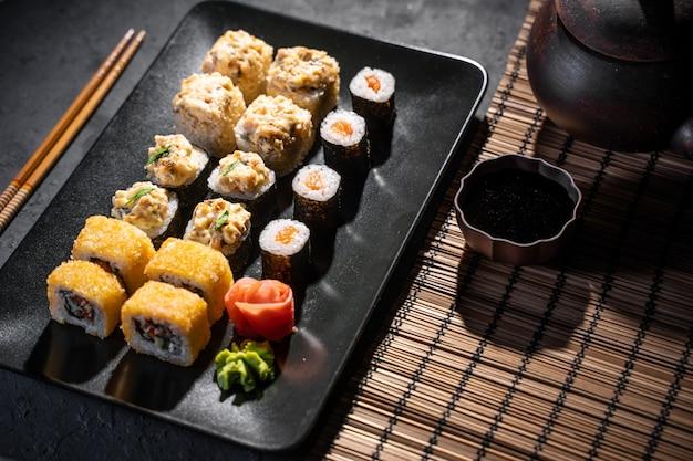 Köstliche sushirollen dienten auf schwarzer tabelle mit essstäbchen Premium Fotos