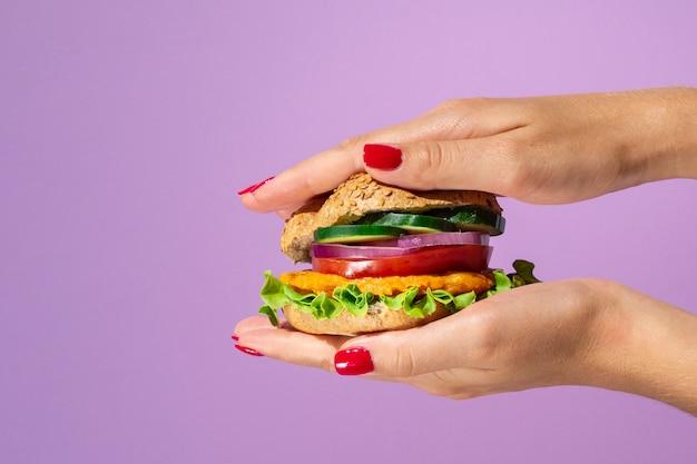 Köstlicher burger auf einem schönen purpurroten hintergrund Kostenlose Fotos