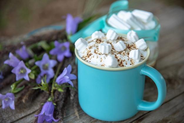 Köstlicher cappuccino mit karamell und marshmallows in einem hellblauen becher. Premium Fotos