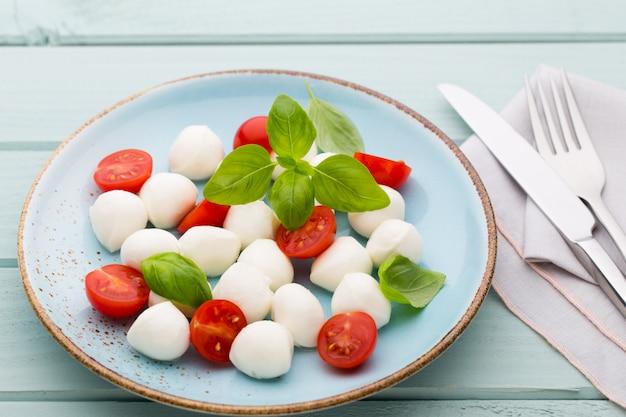 Köstlicher caprese-salat mit reifen kirschtomaten und mini-mozzarella-käsebällchen mit frischen basilikumblättern. Premium Fotos