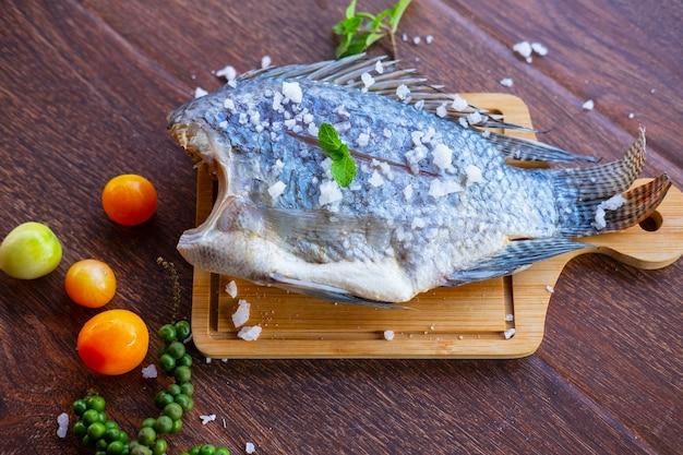 Köstlicher frischer fisch auf dunklem hintergrund. fisch mit aromatischen kräutern, diät oder kochkonzept Premium Fotos