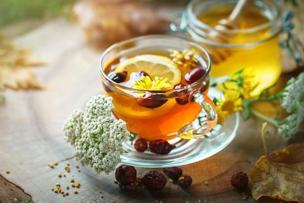 Köstlicher frischer honig und eine tasse gesunden tee mit zitrone und hagebutten Premium Fotos