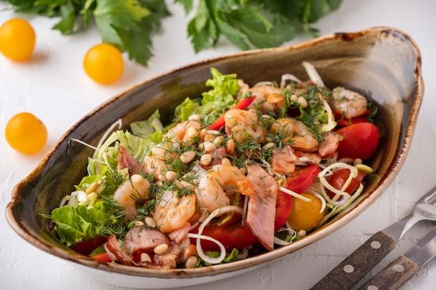 Köstlicher garnelensalat briet speck, gemüse und kiefernnüsse. leckerer meeresfrüchtesalat. Premium Fotos