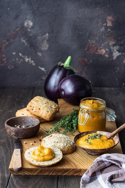 Köstlicher gemüsekaviar in einer hölzernen schüssel und in einem glas diente mit mehrkornbrot. Premium Fotos