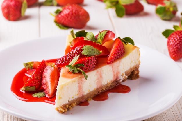 Köstlicher hausgemachter käsekuchen mit erdbeeren auf weißem holztisch. Premium Fotos