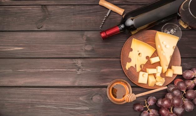 Köstlicher käse der draufsicht mit flasche wein und trauben Kostenlose Fotos