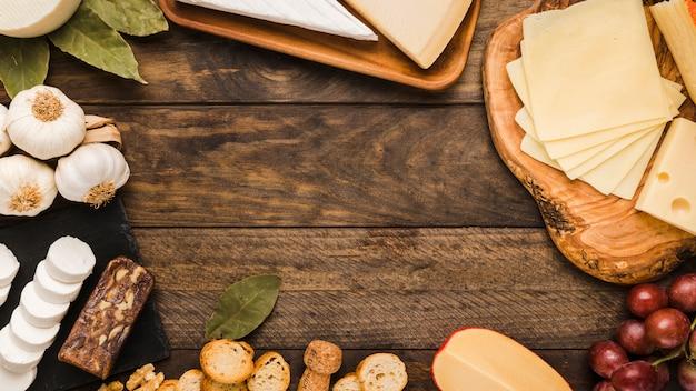 Köstlicher käse mit brotscheibe und roten trauben auf rustikaler tabelle Kostenlose Fotos