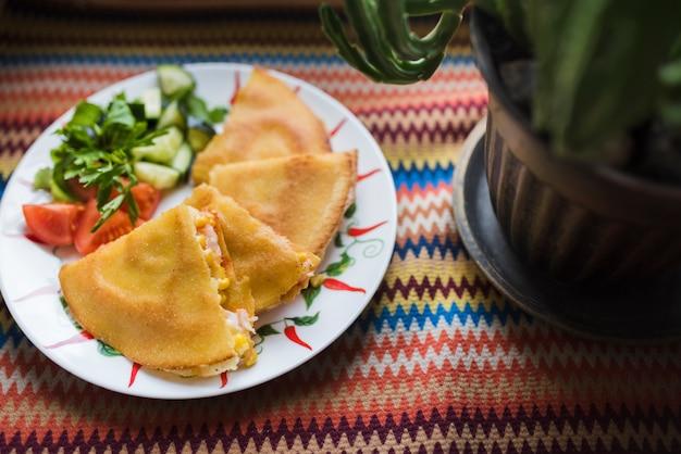 Köstlicher kuchen nahe gemüsesalat auf platte nahe blumentopf Kostenlose Fotos