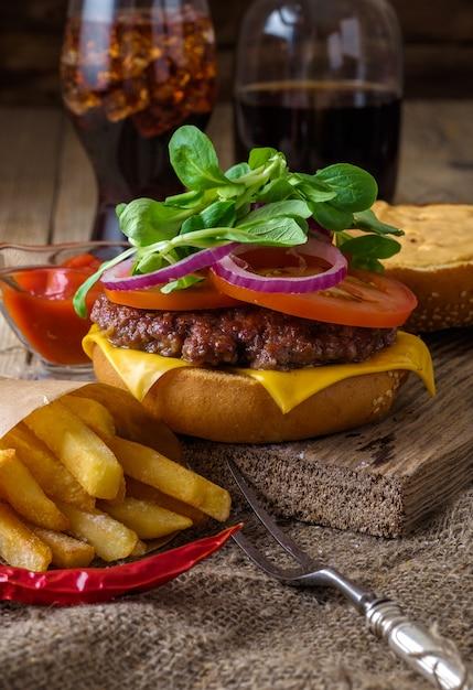 Köstlicher rindfleischburger mit chips und soda auf holztisch. Premium Fotos