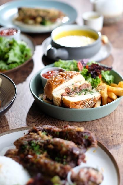 Köstlicher rindfleischburger mit pommes-frites und soße Premium Fotos