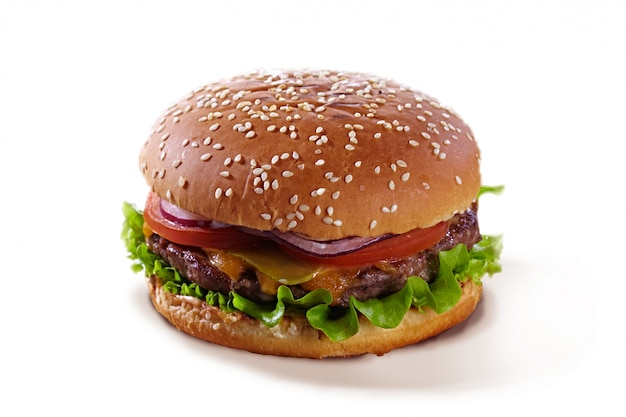 Köstlicher saftiger hamburger mit tomaten, kräutern, käse und fleisch lokalisiert auf einem weißen hintergrund. leckerer burger lokalisiert auf weiß mit sesam. Premium Fotos