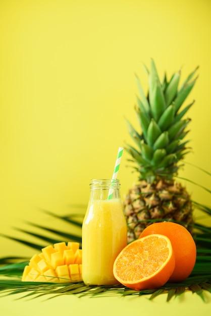Köstlicher saftiger smoothie mit orangenfrucht, mango, ananas. frischer saft im glas über grünen palmblättern. Premium Fotos